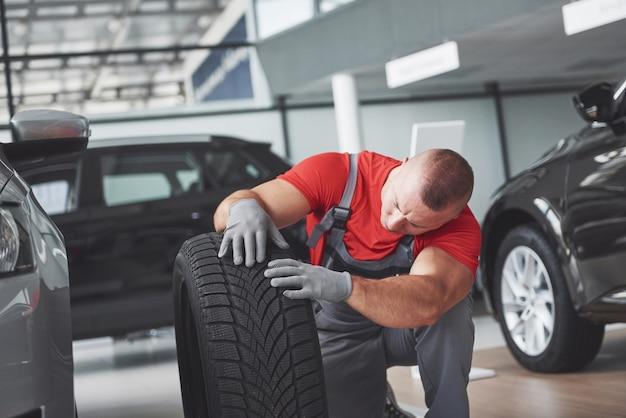Mecánico sosteniendo un neumático en el taller de reparación. sustitución de neumáticos de invierno y verano. Foto gratis