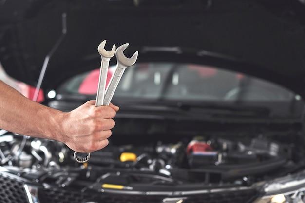 Mecánico sosteniendo un par de llaves en el taller de reparación. Foto gratis