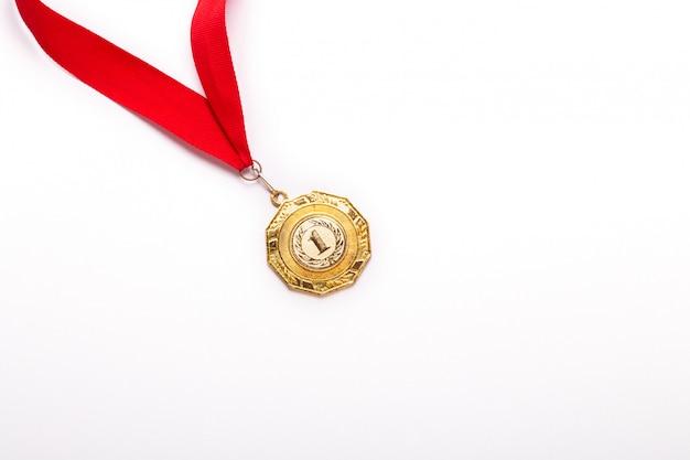 Medalla de oro con cinta roja sobre fondo blanco Foto Premium