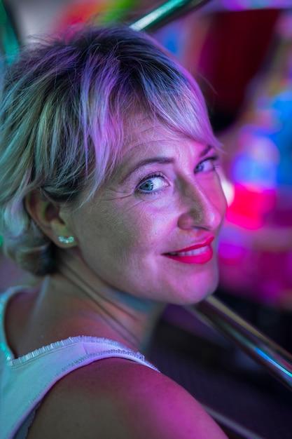 Mediados de edad mujer sonriente preguntándose en lámparas brillantes Foto gratis