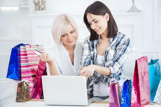 Mediados de mujer adulta y su hija haciendo compras en línea en casa. familia feliz comprando en casa productos de internet. mujeres ordenando en línea. Foto Premium