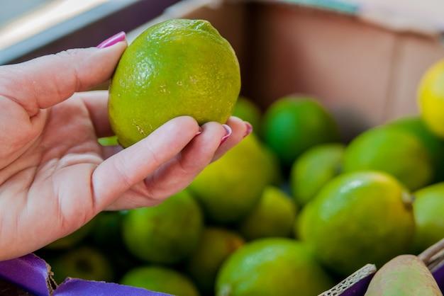 Mediados de la sección de la mujer que compra la cal dulce en el supermercado. mujer que compra las frutas en mercado verde orgánico. mujer, elegir, fresco, cal Foto gratis