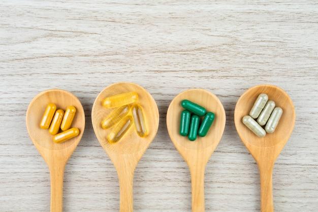 Medicina alternativa a base de hierbas en cápsulas en mesa de madera con espacio de copia para el fondo médico Foto Premium