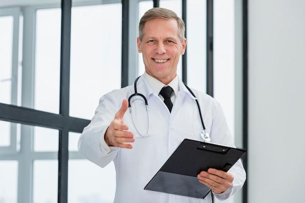 Médico de ángulo bajo con portapapeles Foto gratis