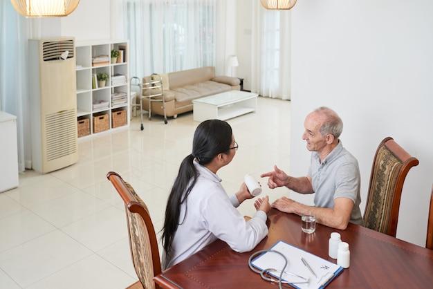 Médico asiático hablando con pacientes caucásicos mayores en casa y discutiendo sobre medicamentos Foto gratis