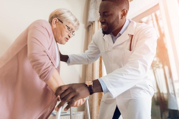 El médico ayuda a salir de la cama a una mujer mayor. Foto Premium