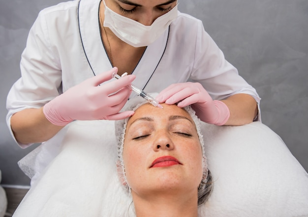 El médico cosmetólogo realiza el procedimiento de inyecciones faciales. mujer joven en un salón de belleza. Foto Premium