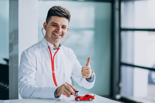 Médico con estetoscopio en una sala de exposición de automóviles Foto gratis