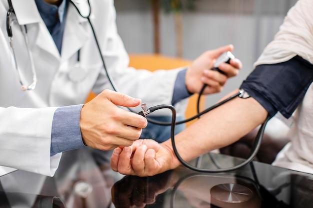 Médico manos midiendo la tensión a un paciente Foto gratis