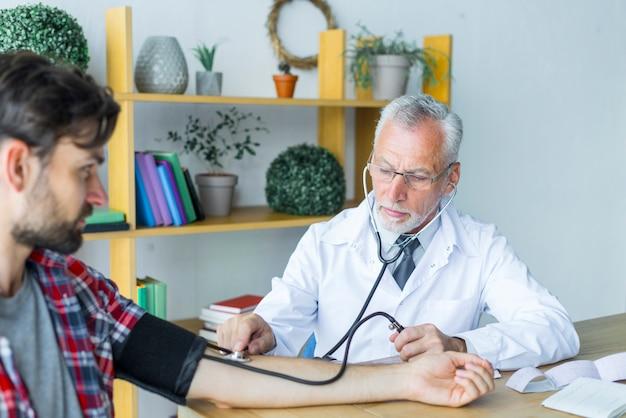 Médico medir la presión arterial del paciente joven Foto gratis