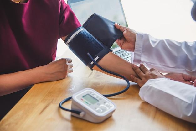 Médico medir la presión sanguínea de su paciente Foto Premium