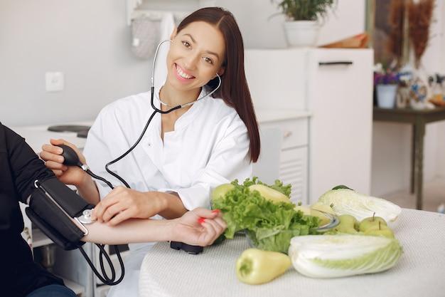 Médico mide la presión del paciente en la cocina. Foto gratis