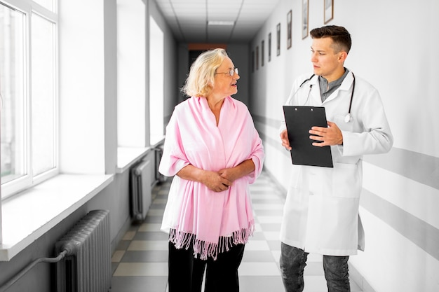 Médico y una mujer caminando en la sala del hospital Foto gratis