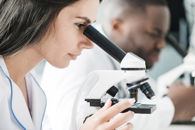 Médico de mujer usando microscopio Foto gratis