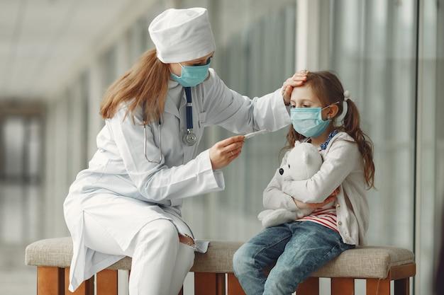 Médico y un niño con máscaras protectoras están en el hospital Foto gratis