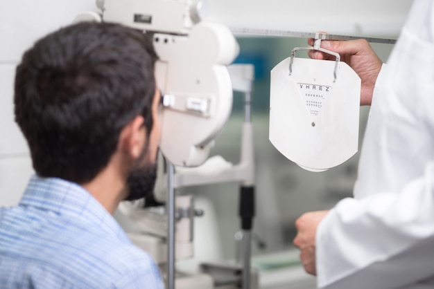 El médico oftalmólogo está revisando la visión ocular de un apuesto joven en una clínica moderna. Foto Premium