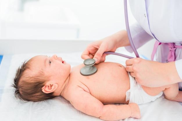 Médico pediatra examina a niña con estetoscopio Foto Premium