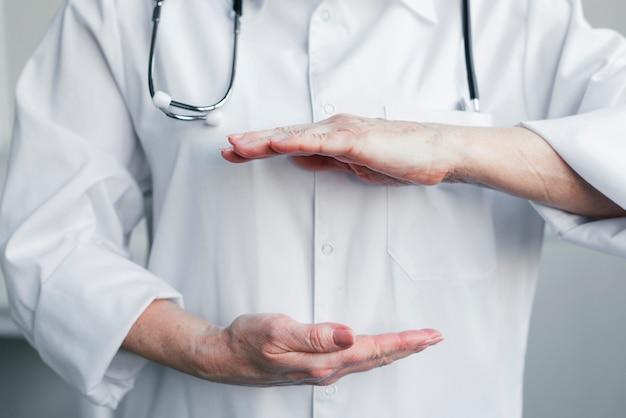 Médico presentando un espacio con sus manos Foto Premium