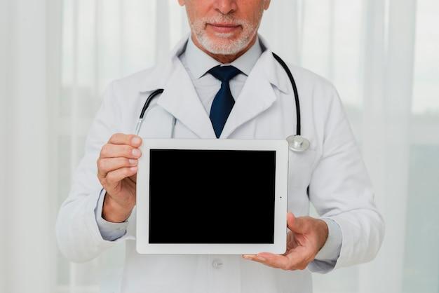 Médico de primer plano que muestra la maqueta de la pantalla de la tableta Foto gratis