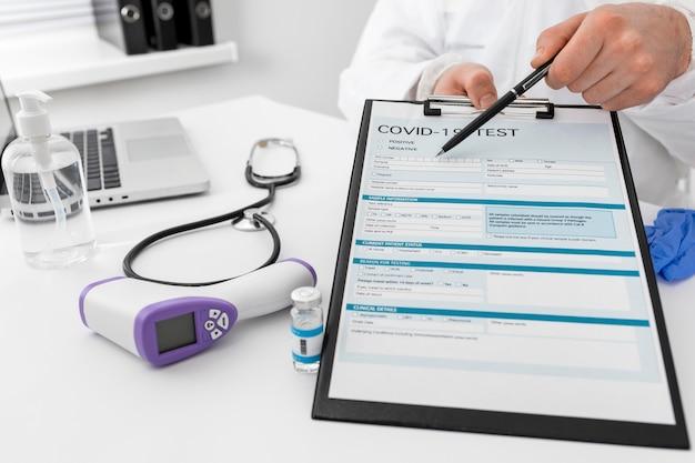 Médico de primer plano que presenta formulario médico covid Foto gratis