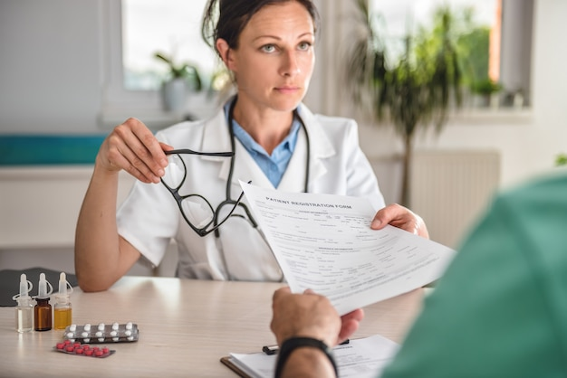 Médico que recibe el formulario de registro del paciente Foto Premium
