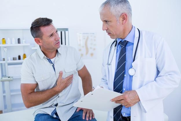Médico serio hablando con su paciente | Foto Premium