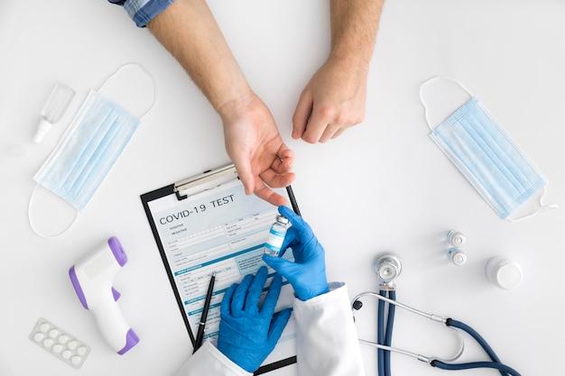 Médico de vista superior dando vacuna covid Foto gratis