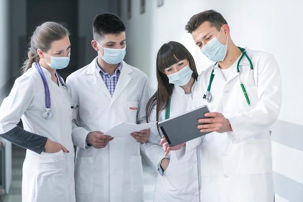 Médicos en máscaras usando tableta Foto gratis