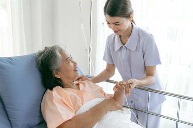 Los médicos se toman de la mano para alentar a las pacientes mayores de edad avanzada en el concepto médico y de atención médica femenina senior del hospital Foto gratis