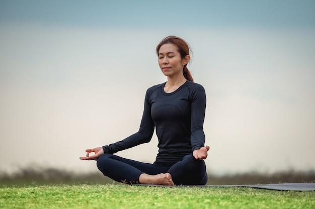 Meditación de yoga asiática femenina en campo abierto | Foto Premium