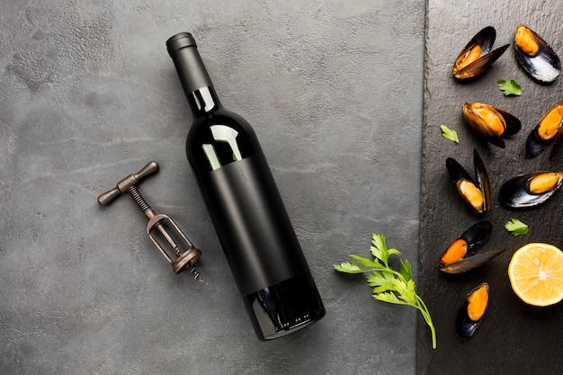Mejillones cocidos en pizarra con botella de vino. Foto gratis