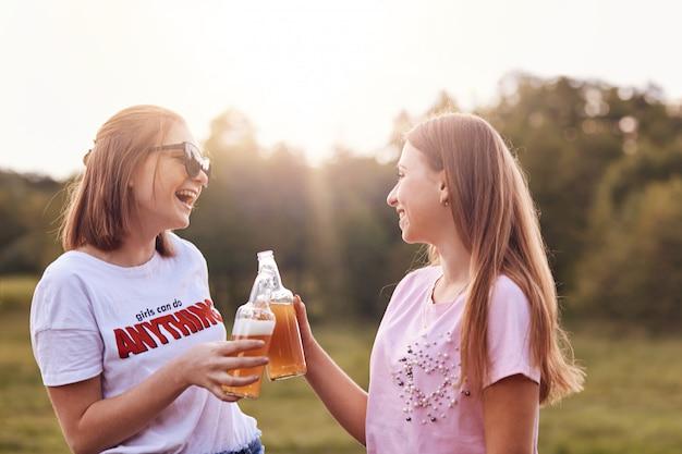 Las mejores amigas brindan con botellas de cerveza fría, se divierten juntas, pasan tiempo libre al aire libre Foto gratis