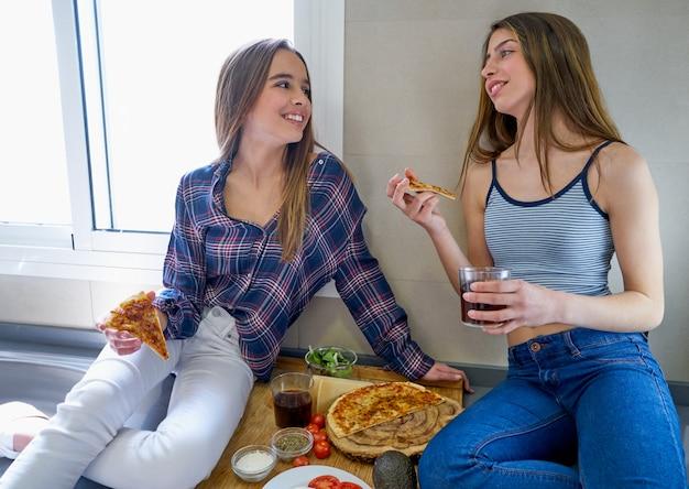 Las mejores amigas que comen pizza en la cocina. Foto Premium