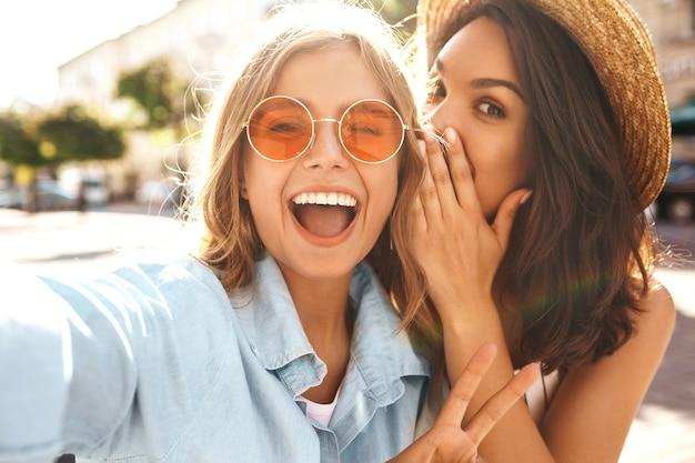 Mejores amigos con atuendo elegante y tomando selfie en la calle Foto gratis