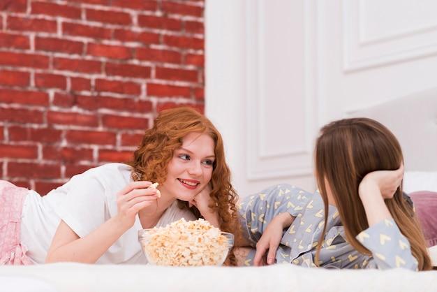 Mejores amigos comiendo palomitas de maíz mientras estás en la cama Foto gratis