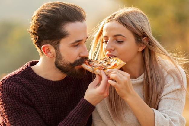 Mejores amigos comiendo una pizza juntos primer plano Foto gratis