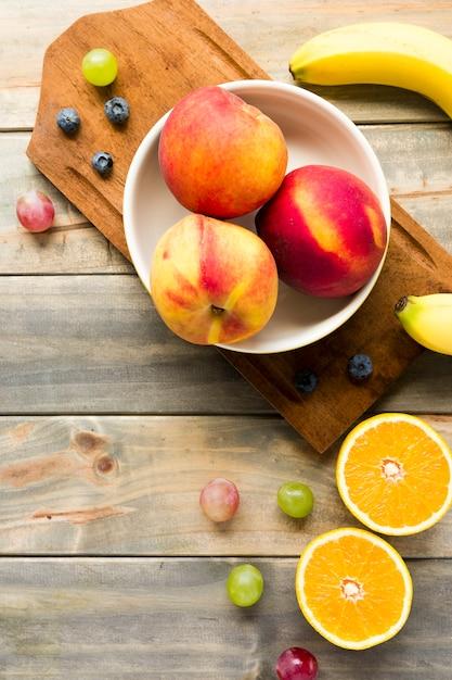 Melocotón; manzanas; uvas; arándanos; plátano y naranjas a la mitad en el  escritorio de madera | Foto Gratis