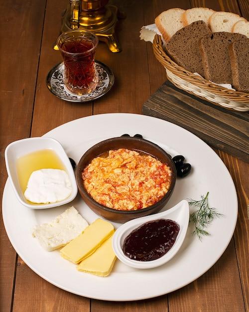 Menemen de desayuno turco con variaciones de miel, crema, aceitunas, mermelada y queso en un plato blanco y un vaso de té Foto gratis