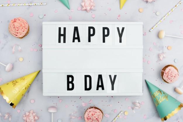 Mensaje de feliz cumpleaños con conos y cupcakes Foto gratis