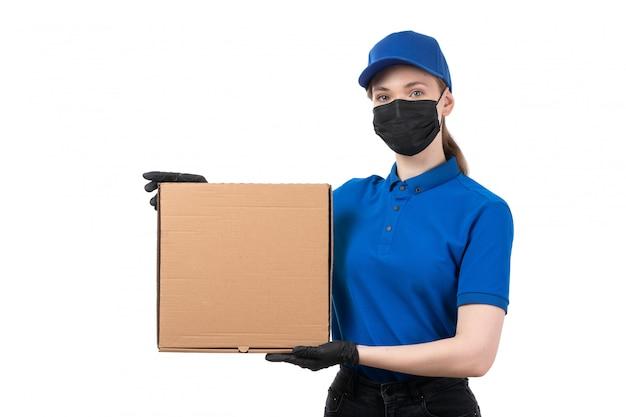 Un mensajero femenino joven de la vista frontal en guantes negros uniformes azules y máscara negra que sostiene el paquete de entrega de alimentos Foto gratis