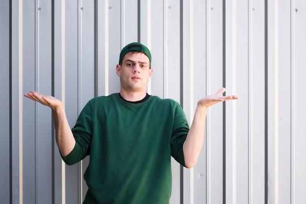 Mensajero joven sin comprender con las manos levantadas. Foto gratis