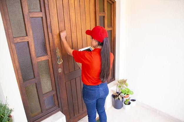 Mensajero latino llamando a la puerta, sosteniendo tabletas y cajas de cartón. repartidora morena de pelo largo en uniforme rojo de pie delante de la puerta y entregando orden. servicio de entrega y concepto de correo. Foto gratis
