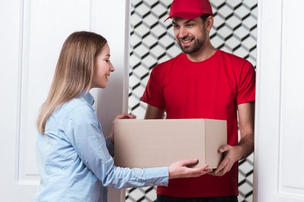 Mensajero que entrega la caja al cliente Foto gratis