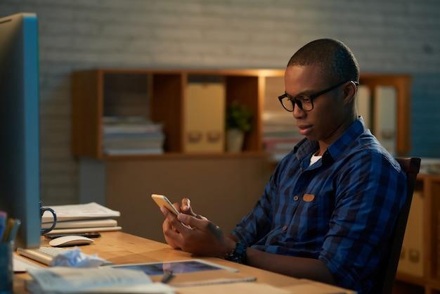 Mensajes de texto con un colega en el teléfono inteligente Foto gratis