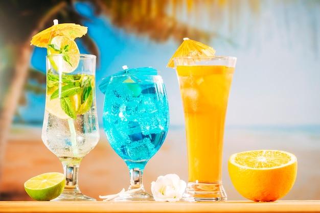 Menta azul naranja bebidas y rodajas de flores blancas cítricas Foto gratis