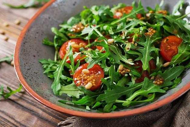 Menú dietético cocina vegana. ensalada saludable con rúcula, tomates y piñones. Foto gratis