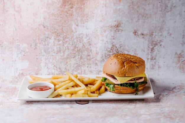 Menú de hamburguesas con papas fritas y salsa de tomate dentro de un plato blanco. Foto gratis