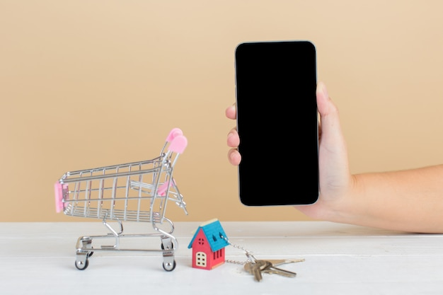 Mercado inmobiliario con casa, carrito de compras y teléfono. Foto gratis