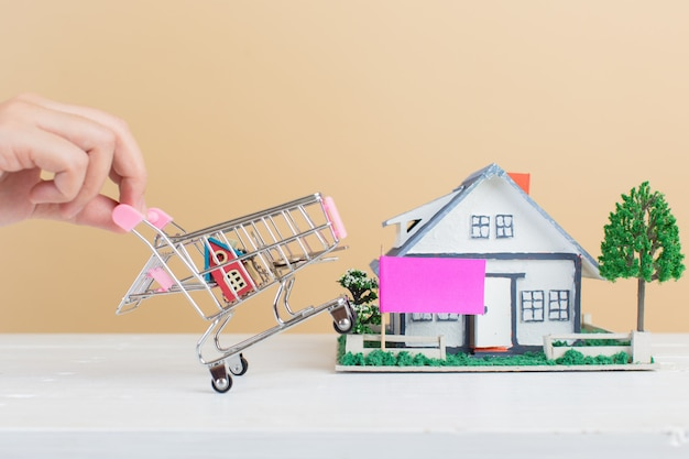 Mercado inmobiliario, casa en carrito de compras Foto gratis
