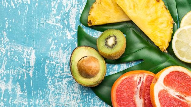 Merienda de frutas y vitaminas en hoja monstera Foto gratis